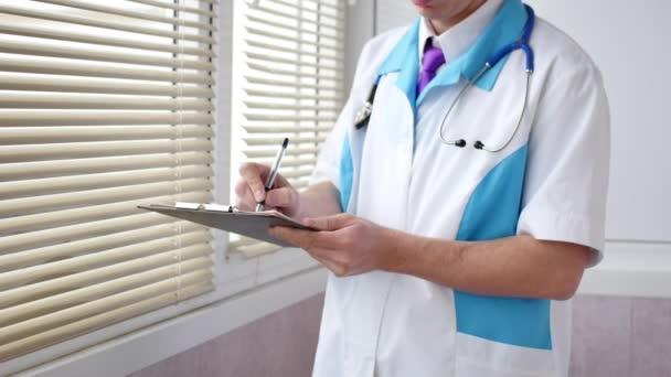ein Arzt füllt medizinische Formulare auf einem Klemmbrett aus, Nahaufnahme. Gesundheits-, Versicherungs- und Medizinkonzept.