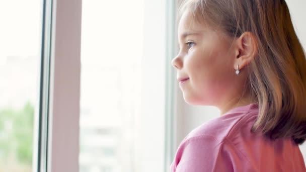 Portrét dítěte, které se dívá z okna
