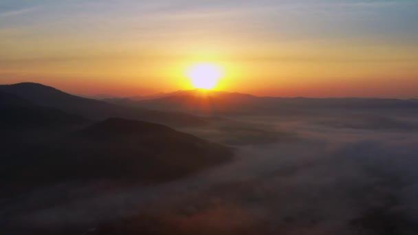 Lenyűgöző táj - napkelte a tenger és a hegyek közepette a felhők