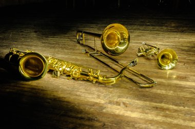 Brass and wind instruments - saxophone, trombone, trumpet on stage with backlight