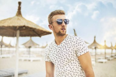 Outdoor portrait of a handsome guy in sunglasses resting and having fun on a sunny beach