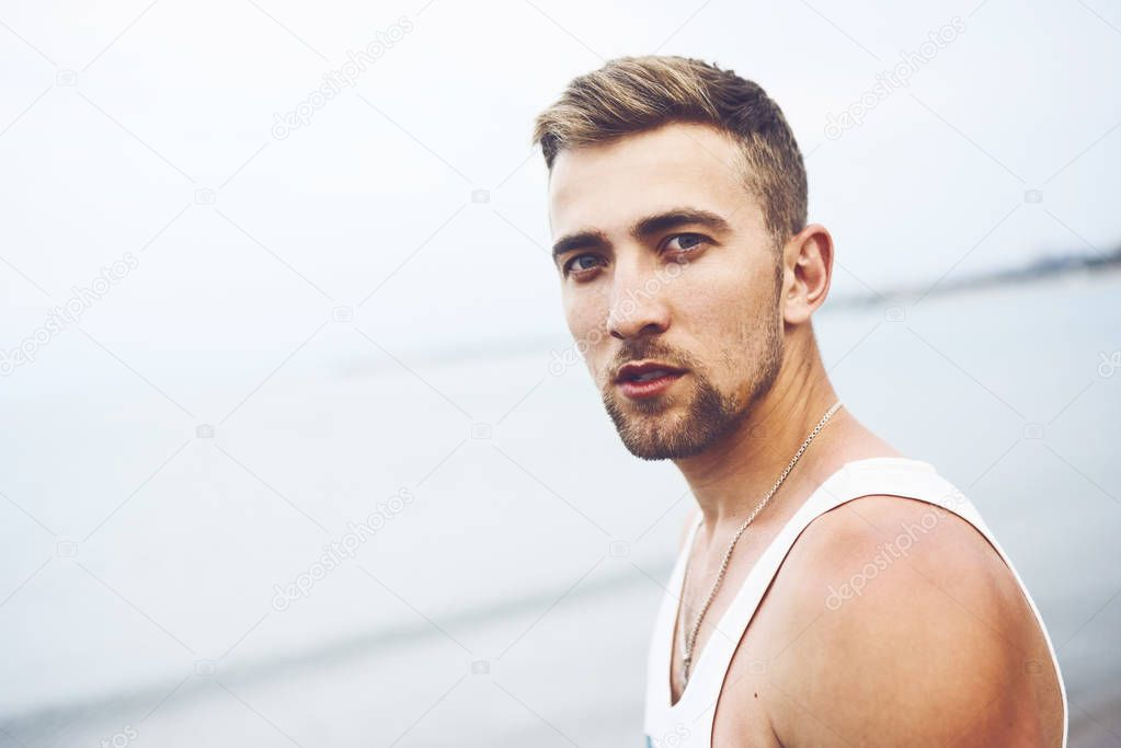 Outdoor lifestyle portrait with young handsome guy on the beach