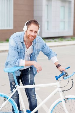 Casual guy next to a vintage bicycle listening music with headphones wearing denim shirt