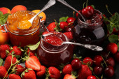 Photo assortment of jams, seasonal berries, apricot, mint and fruits.