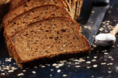 bread cutted on board from above on dark. Kitchen or bakery post