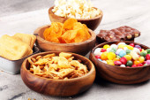 Salty snacks. Pretzels, chips, crackers in wooden bowls and cand