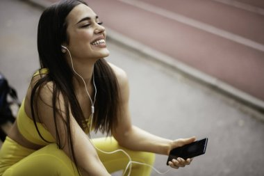 happy woman in sportive clothes at running track listening music from smartphone with earphones