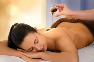 Close up of young woman having antioxidant chocolate cosmetic treatment in spa.Therapist pouring hot cacao massage oil on girls back.