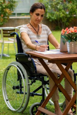 Close up portrait of young handicapped girl in wheelchair outdoors.Woman sitting at table with laptop, pen and paper in garden.