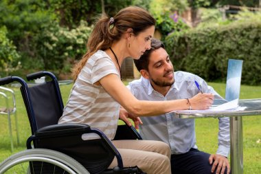 Close up portrait of disabled young woman in wheelchair working with partner in garden. Young man assisting girl with work on laptop.