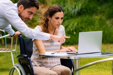 Close up portrait of disabled young woman in wheelchair working with male partner on laptop in garden.