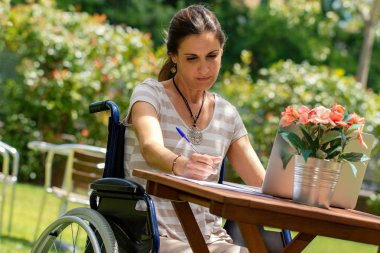 Close up portrait of young disabled woman in wheelchair working on laptop in garden.