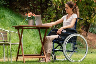Full length portrait of young paralysed woman in wheelchair sitting at table outdoors. Side view of girl working on laptop in garde.