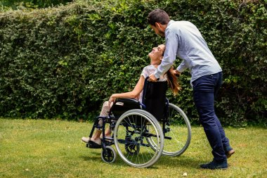 Young man pushing disabled girl in wheelchair outdoors. Side view of couple laughing  together in park.