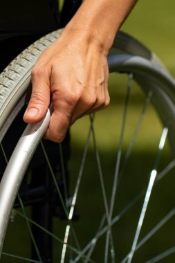 Close up of detail of female hand holding rail on wheelchair outdoors.