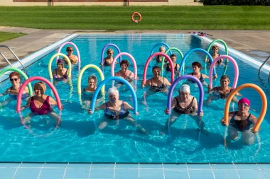 Front view portrait of senior aqua gym class with foam noodles. Sportive ladies standing together in outdoor swimming pool.