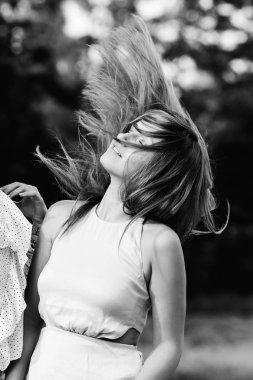 A beautiful girl closed her eyes and wiggles her hair on black and white photography