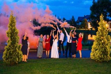 Yeni evliler ve konuklar ellerini yukarı kaldırdı ve sis bombası turuncu renkli duman ile göl ve binalar karşı tutun