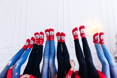 Girls legs raised up on a white wall background. jeans and red s