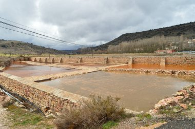 Pool, Pond, Arches And Ferris Wheels Made In Ashlar And Manposteria Of The Salinas In Imon With Its Beautiful Brown Color. Architecture, Science, Geology, Travel. March 18, 2016. Imon, La Alcarria, Guadalajara, Castilla La Mancha, Spain.