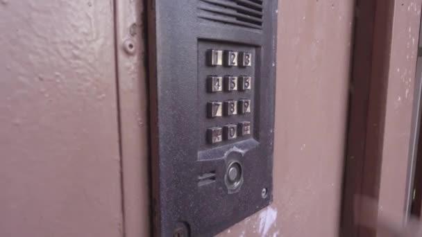 eine Person öffnet die Tür durch Eingabe eines Zahlencodes.