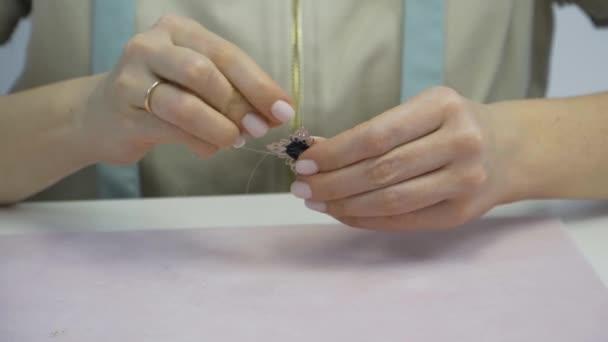 Cucito ragazza cuce perline a spilla.