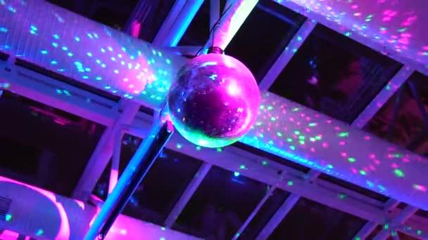 Disco labdát forog a mennyezet alatt egy szórakozóhely, csillog, és tükrözi a színes fény, vibrálás villog és lézeres villám kék, rózsaszín és lila színek.