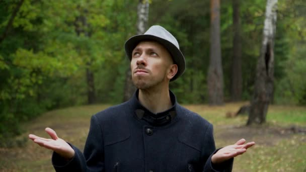 die Reaktion des Mannes mit Hut und Mantel, als plötzlich der Regen einsetzte.