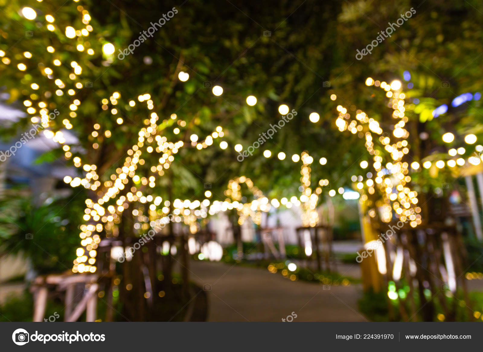 Blurred image Decorative outdoor string lights hanging on tree in the garden at night time - decorative Christmas lights - happy new year– stock image