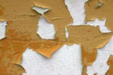 A wall with peeling plaster orange color