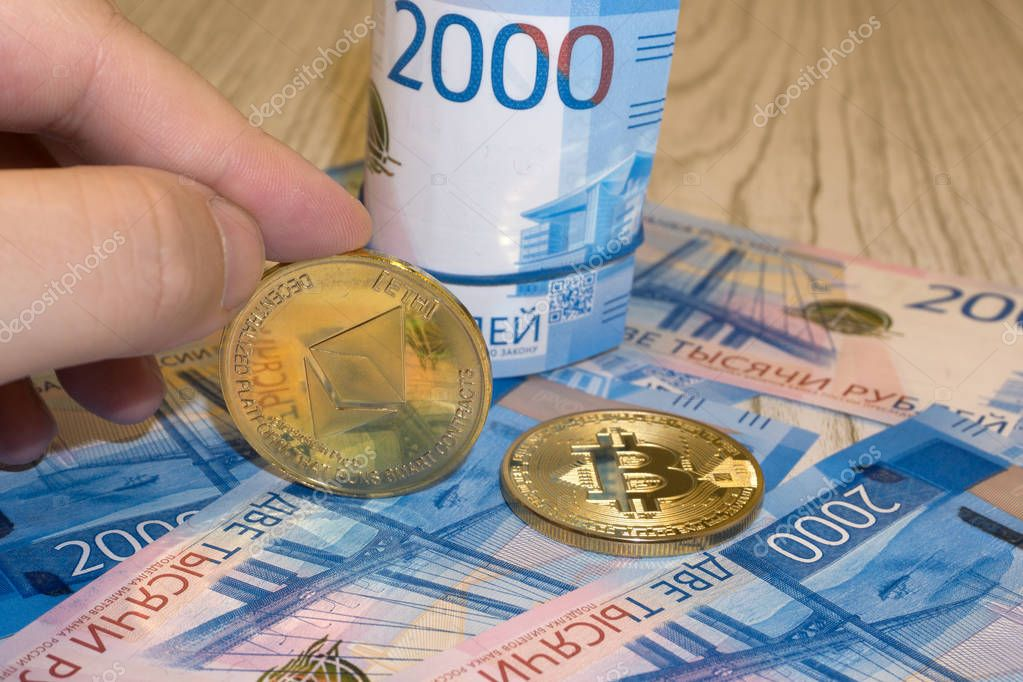 Gold krypto coins bitcoin BTC, paper notes of Russian rubles. Metal coins are laid out in a background to each other, close-up view from top, crypto currency exchange of money