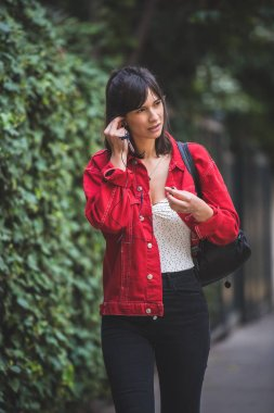 Young woman wearing a red jacket and listening to music with her ear phones