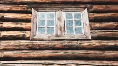 Dark timbered wooden wall with window. Old building.
