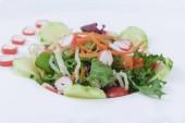 Vegyes hajtások saláta hagyma aprított sárgarépa, cseresznye paradicsom egy üveglapra. Fehér háttér