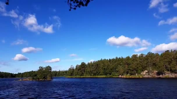 Time lapse. View of gorgeous nature landscape on a windy summer day. Beautiful lake, green forest and blue sky with white clouds. Sweden, Europe.