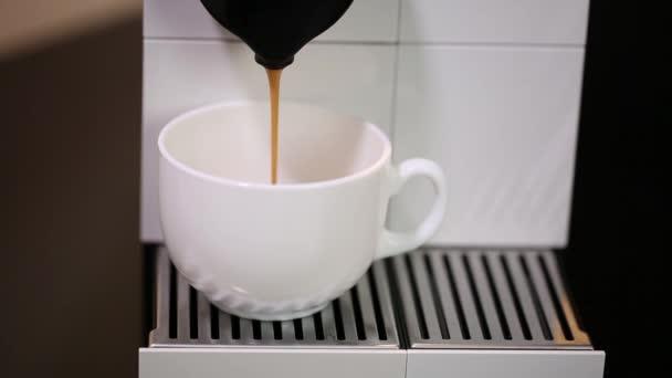 Nahaufnahme des Kaffees, der aus der Kapselkaffeemaschine in die weiße Tasse läuft. Schöne Hintergründe.