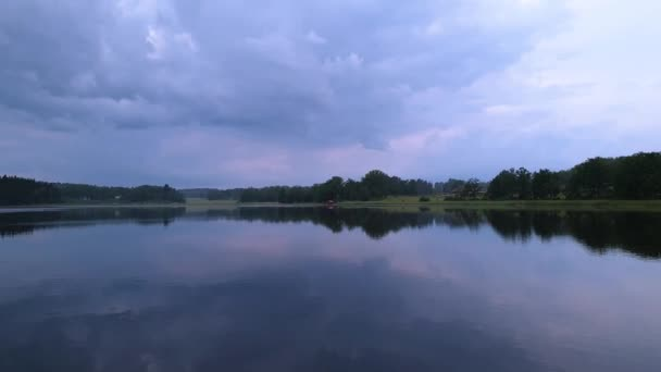 Gorgeous view of nature landscape on calm summer evening. Lake shore with green trees and plants reflecting in crystal clean mirror water surface. Sky covered with heavy thunder clouds. Beautiful back
