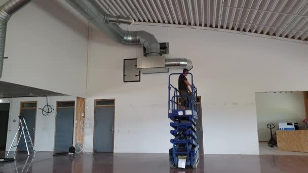 Pracující muž v nůžkovském zvednutí stropu. Koncepce stavebních prací.