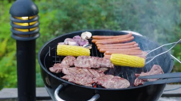 Zblízka pohled na muže grilující maso steak, kukuřice, klobásy a cibule venku za letního dne. Zdravá výživa. Švédsko.