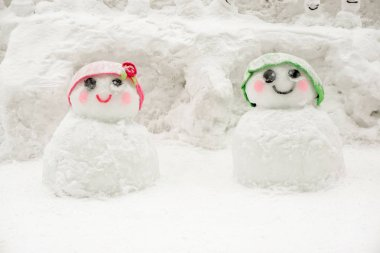 Boy and girl cute snowman kid wearing green and pink wool hat show for tourist snap photo in the Otaru Snow Light Path Festival at Otaru, Hokkaido prefecture, Japan