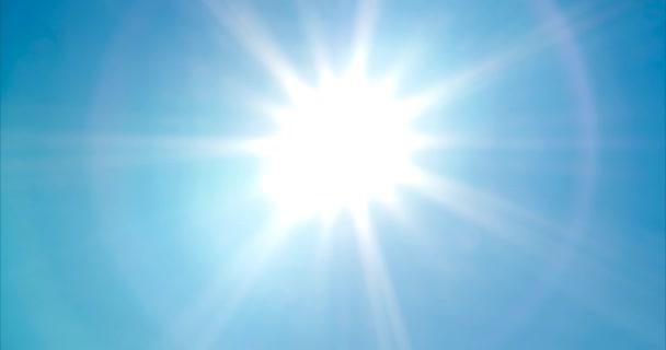 Felnézett világos, élénk nap a napsugarak és a lencse fáklyát a kék nyári égen