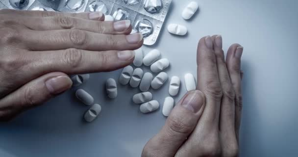 Hands covers and hiding many white prescription drugs, medicine tablets or vitamin pills in a pile - Concept of healthcare, opioids addiction, shame, medicament abuse or medication treatment