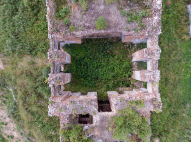 View of an abandoned brick building with a drone, a forest grows inside