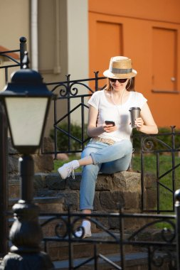 Happy young woman wearing casual clothes sitting on the staircase in the old town with a phone and a cup of coffee