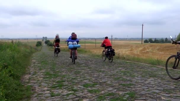 Skupina cyklistů pokračuje podél staré silnice kámen