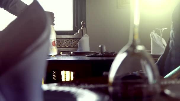 Číšník servíruje stůl v restauraci