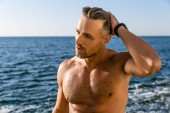 handsome wet adult man looking away on seashore