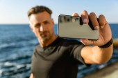 Fotografie close-up portrait of adult man taking selfie with smartphone on seashore