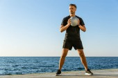 Photo handsome adult sportsman working out with fit ball on seashore