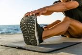 Fotografie Schuss von sportlicher Mann stretching am Meeresstrand beschnitten